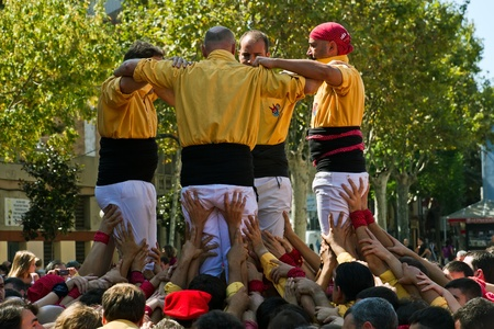 BARCELONA - SEPTEMBER 11: Some unidentified people called Castellers do a Castell or Human Tower, typical tradition in Catalonia, on September 11, 2011 in Badalona, Spain.  Stock Photo - 11400896