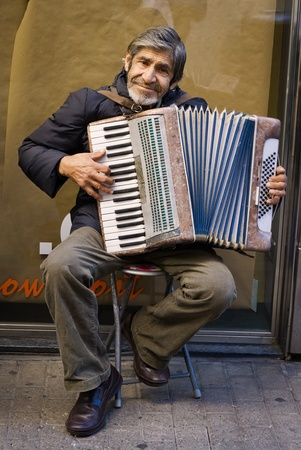 BARCELONA - DECEMBER 08: The old man sits with his accordion and play music to earn some money. Are effects of the crisis. On December 8, 2011 in Barcelona, Spain,.