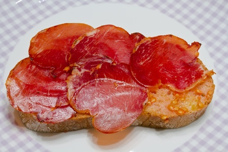 Catalan-style tomato rubbed on a slice of bread with oil and salt point, about the scourge of rural style. Stock Photo - 11739813