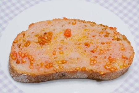 Catalan-style tomato rubbed on a slice of bread with oil and salt point photo