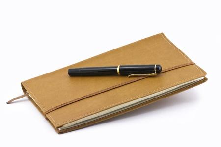 Leather notebook e penna isolato su sfondo bianco photo