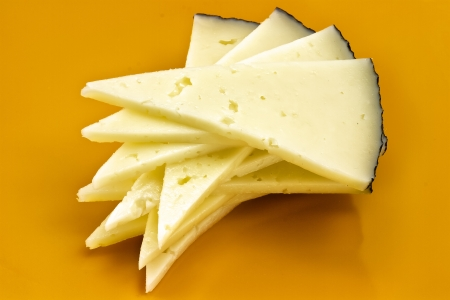 some slices of manchego cheese, typical of Spain, isolated on a white background  photo