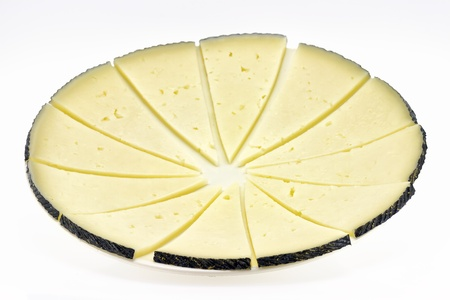 cows milk cheese: some slices of manchego cheese, typical of Spain, isolated on a white background