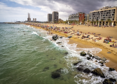 BARCELONA, SPAIN - JULY 15  Barcelona beachfront, considered between 10 best urban beaches of the world, crowded of people on summertime on Barceloneta, July 15, 2012 in Barcelona, Spain