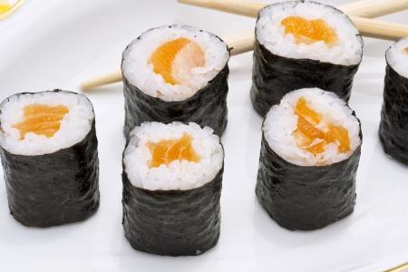 Makizushi  Delicious sushi rolls on white plate with chopsticks and wasabi  Maki