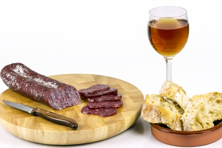precedent: Iberian sausage sausage on a wooden board, with a glass of wine, and sliced   rustic bread  Stock Photo