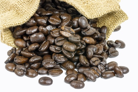 Roasted coffee beans in jute sack on white background  photo