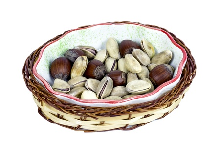 hazelnuts and pistachios in a wicker basket in bowl isolated on white background  photo