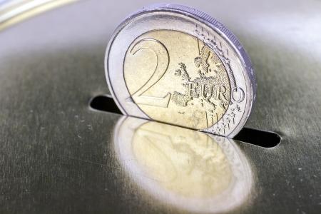 Deux-pièces en euros de l'insérer dans une tirelire l'épargne