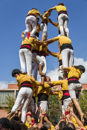 BARCELONA - SEPTEMBER 11: Some unidentified people called Castellers do a Castell or Human Tower, typical tradition in Catalonia, on September 11, 2012 in Barcelona, Spain.