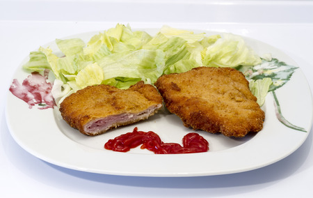 Chicken cordon blue with lettuce on white plate photo