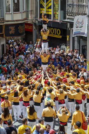 BARCELONA, SPAIN - MAY 19: Some unidentified people called Castellers do a Castell or Human Tower, typical tradition in Catalonia, on May 19, 2013 in Barcelona, Spain.