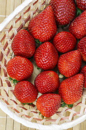 wicker basket with a group of fresh and juicy strawberries photo