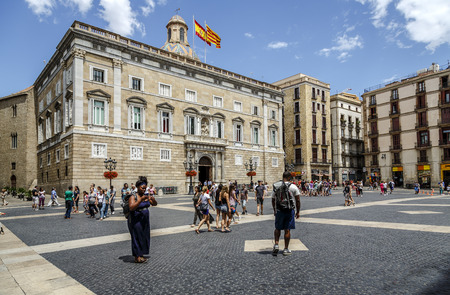 generalitat: BARCELONA, SPAIN - JUNE 29,2014: tourists walking on the the Palau de la Generalitat is a medieval buiding that houses the offices of the Presidency of the Generalitat de Catalunya,  in Barcelona, Spain Editorial