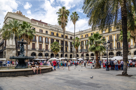 BARCELONA - JUNE 29, 2014: Tourists on Plaza Real in Barcelona, Spain. The Royal Plaza is a square in the Gothic Quarter. Located next to La Rambla and is a well-known tourist attraction. All holidays, collectors gather to buy stamps and coin collection.