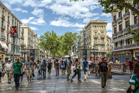 BARCELONA, SPAIN - JUNE 29,2014: Tourists walk famous Rambla street in Barcelona, Spain. According to Mastercard, Barcelona is the 15th most visited city worldwide (8.8m in 2013).