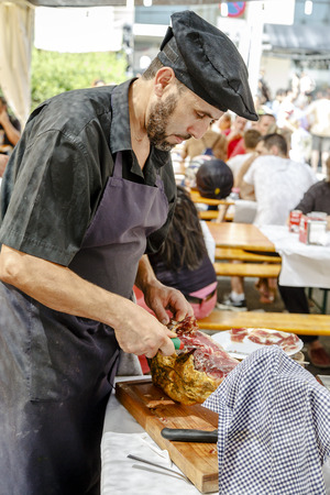 BARCELONA, SPAIN - JULY 05, 2014: unidentified person cutting ham, very typical in Spain in BARCELONA HARLEYS DAYS 2014