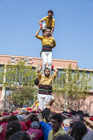 BADALONA, SPAIN - SEPTEMBER 11, 2014: Some unidentified people called Castellers do a Castell or Human Tower, typical tradition in Catalonia. Celebrating National Day the Catalan National
