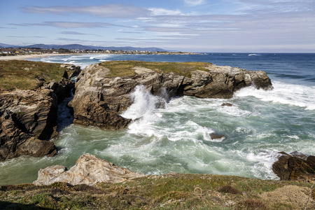 big and small: Las Catedrales beach in Galicia, Spain. Paradise beach in Ribadeo, Spain In the background Foz