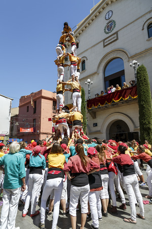 traditional climbing: Badalona, Spain - May 17, 2015: Some unidentified people called Castellers do a Castell or Human Tower, typical tradition in Catalonia, in Badalona Barcelona, Spain. Editorial
