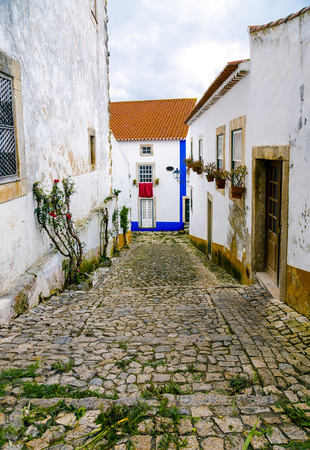 fortified wall: Obidos, Portugal, a medieval city encircled by a fortified wall. Its streets, squares, walls and its massive castle have turned the picturesque village into a preferred tourist attraction in Portugal. Stock Photo