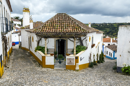 fortified wall: Obidos, Portugal - March 20 , 2016: Obidos, Portugal, a medieval city encircled by a fortified wall. Its streets, squares, walls and its massive castle have turned the picturesque village into a preferred tourist attraction in Portugal.