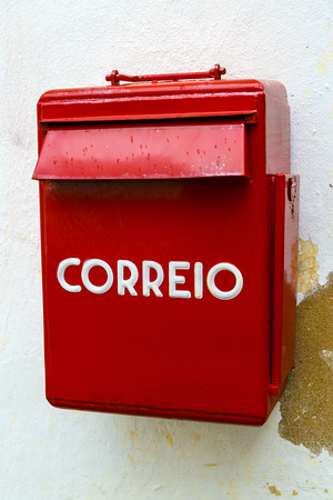 intense: S mailbox typical Portuguese post in Obidos Portugal, striking for its intense red