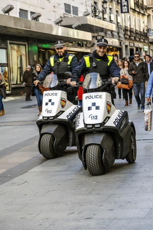 motorcycle officer: Madrid, Spain - November 27, 2015: Police patrol Madrid with his new electric motorcycle, do not pollute not make noise and are very well received by people.