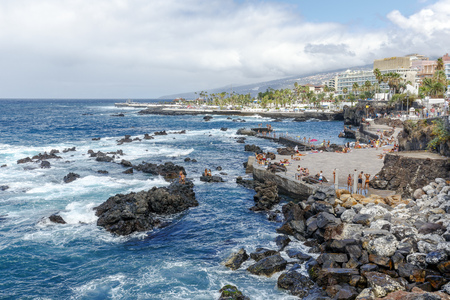 Puerto de la Cruz, Spain - August 16, 2015: Tourists enjoy the good weather and relax on the beach of San Telmo in the Atlantic Ocean, Puerto de la Cruz, Tenerife, Canary Islands, Spain Stok Fotoğraf - 60580714