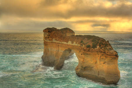 Ocean water splashing on London Bridge, a natural rock formation, along Great Ocean Road in Australia. photo
