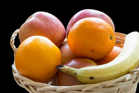 Basket of fruits on black background, containing oranges, apples and bananas photo