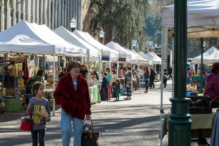 Many people at Portland farmers market in Oregon on a sunny day. People can be seen laughing standing listening looking walking and smiling. Local business owners offering samples answering questions and making sales to customers from their tents or kios Editorial