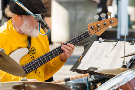 Portland musician Ray Mann of band Boomeration performing live music on stage at a farmers market in Portland Oregon playing guitar drums and singing simultaneously Editorial