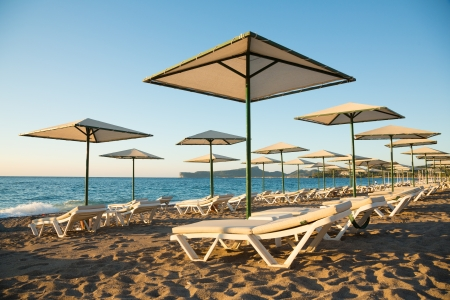 Empty beautiful sunny beach in the morning with umbrellas and beach beds Stock Photo