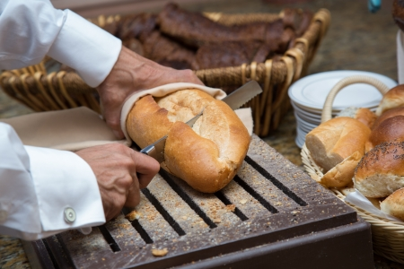 Mans hand cutting bread on a wooden board with a knife