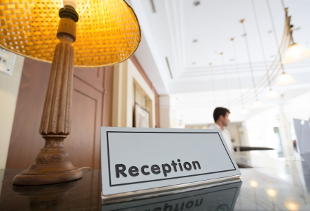 Hotel reception desk with a table and receptionists on a background Stock Photo