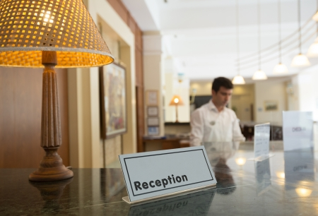 Hotel reception desk with a table and receptionists on a background Stock Photo - 18310864