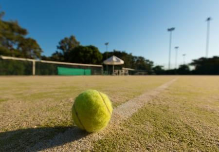 Tennis ball on a line of a green tennis court