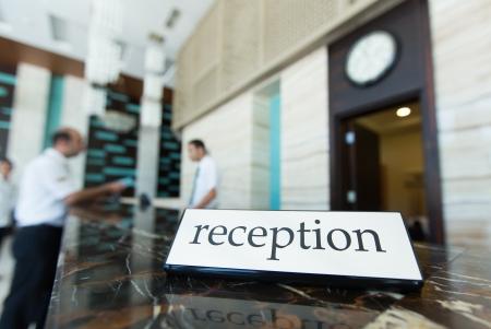 hotel reception: Rezeption des Hotels mit einem Tisch und Rezeptionisten auf einem Hintergrund Lizenzfreie Bilder