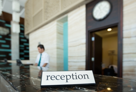 Hotel reception desk with a table and receptionists on a background photo