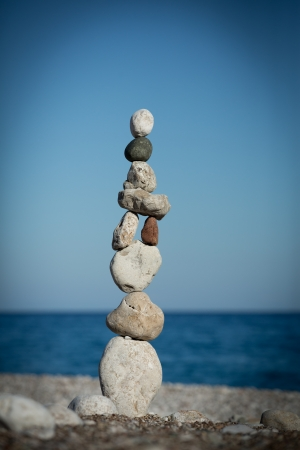 Stack of sea stones (pebbles) balancing on a sea and sky background
