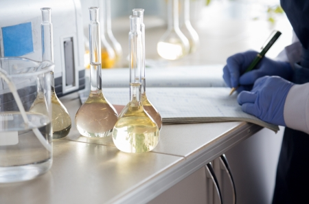 Flasks with liquid in a laboratory  Scientist writes down the result of laboratory tests flask