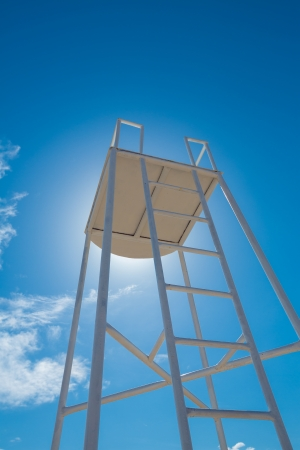 Lifeguard watch tower over s beep blue sky in a shiny day Stock Photo