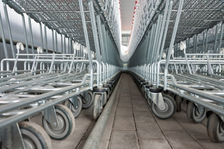 Rows of empty metal shopping carts in a supermarket photo