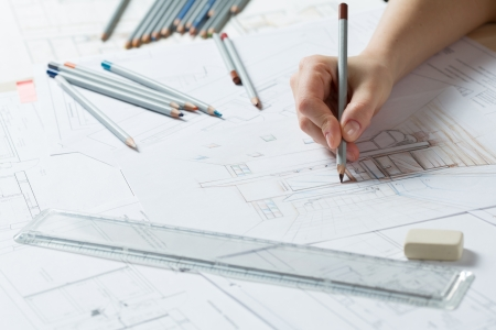 Interior designer works on a hand drawing sketch using color pencils, rule and rubber Stock Photo - 18490081