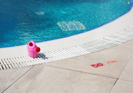 Toy pink watering can on the edge of kids swimming pool with an indicator of a pool depth