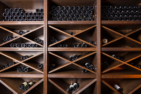 Wine cellar with bottles on wooden shelves