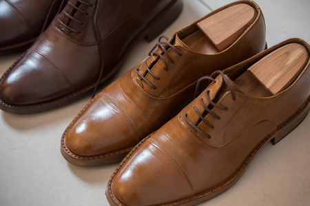 Two pairs of brown handmade classic mens shoes  with a shoe pads and stretchers inside and beside the shoes Stock Photo