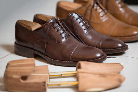 Two pairs of brown handmade classic mens shoes  with a shoe pads and stretchers inside and beside the shoes photo