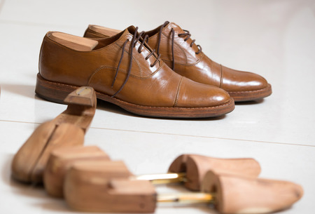 Pair of brown handmade classic mens shoes  with a shoe pads and stretchers inside and beside the shoes